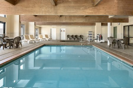 Sparkling indoor pool surrounded by tables and chairs