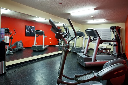 Fitness center with red wall and mirrored wall