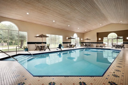 Indoor pool area with patio furniture and large windows