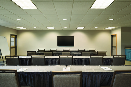 Meeting room with tables and chairs arranged classroom style in front of a flat-screen TV