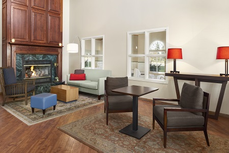 Modern lobby with a fireplace, comfortable seating and red accents