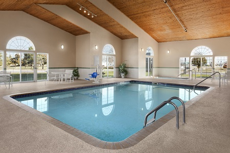 Indoor pool and hot tub surrounded by white deck chairs