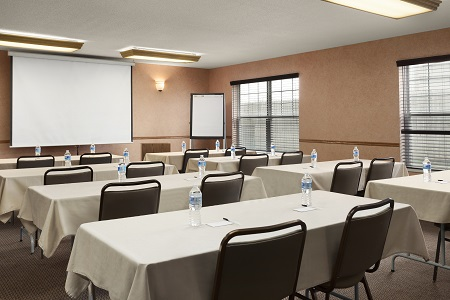 Meeting room with rows of tables and chairs facing a presentation screen