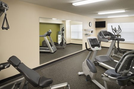 Hotel fitness center with a large mirror and a flat-screen TV