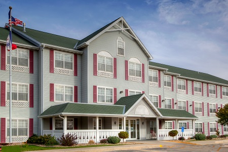 Exterior of the Country Inn & Suites, Waterloo, IA with red shutters