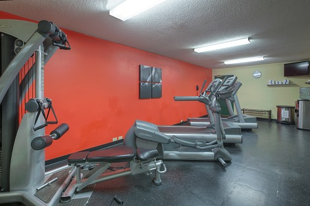 Fitness center with cardio equipment and a red accent wall