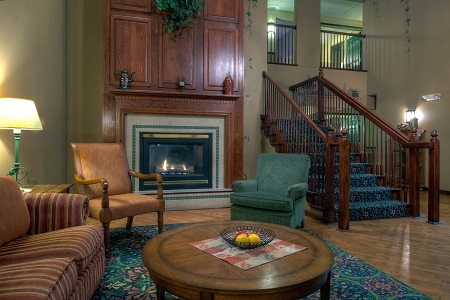Welcoming hotel lobby with a fireplace, a patterned couch and two armchairs