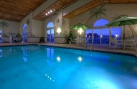 Hotel's indoor pool surrounded by white chairs