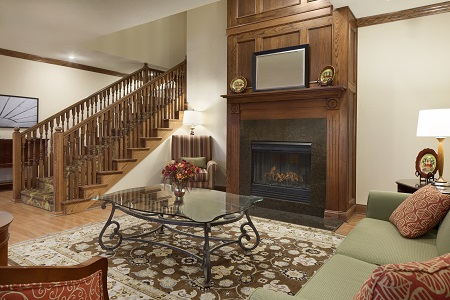 Lobby with a fireplace and seating beside the staircase