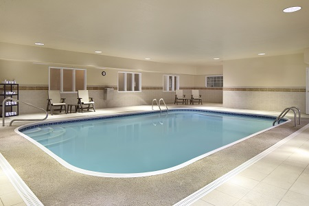 Heated indoor pool with chairs and towel rack