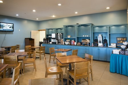 Hotel breakfast room with wooden tables and chairs, blue cabinets and a variety of breakfast items