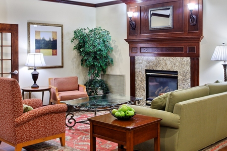 Lobby with fireplace, green couch and red armchairs