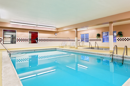 Indoor pool and hot tub with checkered tiles on the wall