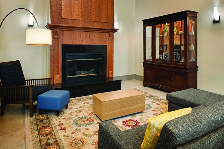Hotel lobby with a gray sectional, a dark blue armchair, a fireplace and a wooden display case