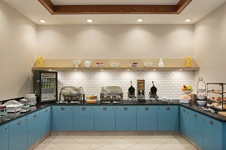 Breakfast area with blue cabinets, hot entrées, pastries and two waffle irons