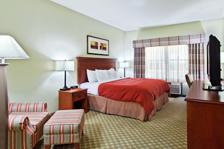 Hotel Room With King Bed And Plush Chair