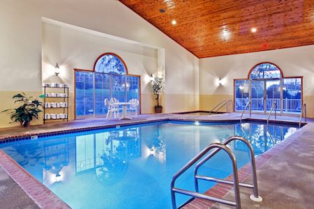 Hotel's indoor pool and hot tub area with natural light