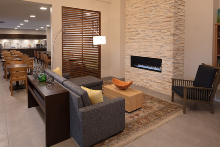 Hotel lobby with a fireplace, a gray sofa and an attached breakfast room