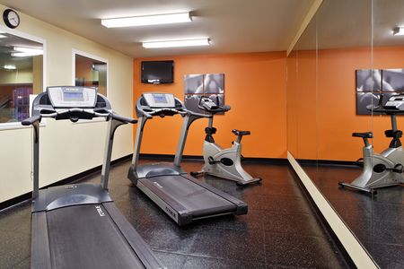 Cardio machines, mirrors and a TV in the fitness center