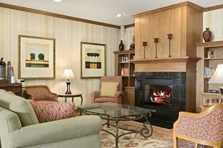 Hotel lobby with a couch and chairs around the fireplace