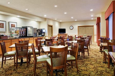 Breakfast area with tables, chairs and flat-screen TV