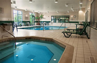 Indoor pool and hot tub with green lounge chairs