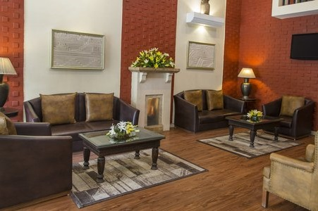 Welcoming hotel lobby with brown couches, chairs and tables