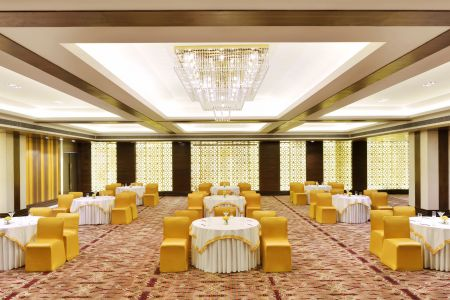 Banquet hall set with white tables and yellow chairs