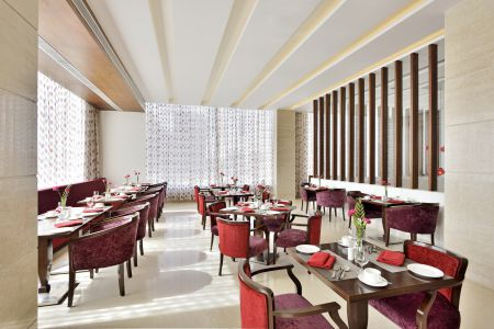 Restaurant featuring red velvet chairs and ample natural lighting