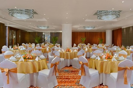 Banquet hall with round tables draped with gold linens