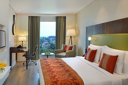 Superior Room with a king bed, colourful bedding and flat-screen TV