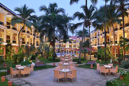 Tropical hotel courtyard with table seating, benches and palm trees