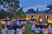 Linen-topped round tables on the lawn at our Mysuru hotel