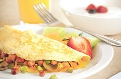 Omelette and fresh fruit served on classic diningware