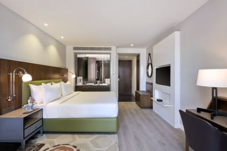 Spacious guest room featuring wood flooring and a king bed with white linens