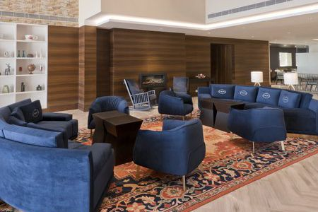 Welcoming lobby with a fireplace and blue sofas and armchairs