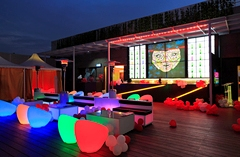 Brightly lit, colourful chairs in front of bar