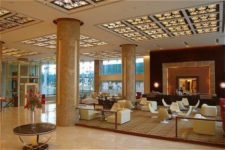 Sahibabad hotel lobby with gold columns and white chairs