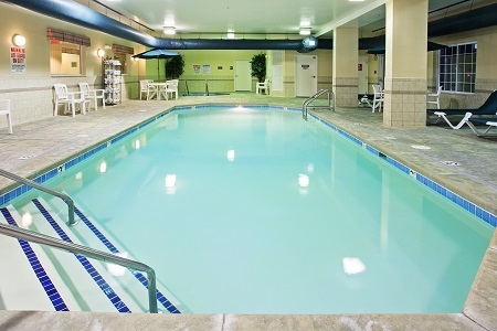 Spacious indoor pool with chairs and fresh towel station