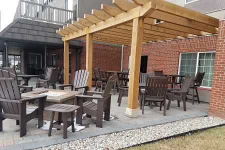 Outdoor patio featuring a fire pit and wooden chairs