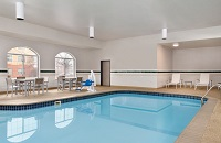 Indoor pool area with tables, chairs and a pool lift