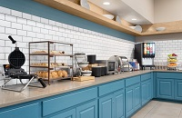 Dining area with blue cabinets, assorted breads, fruit and a waffle iron