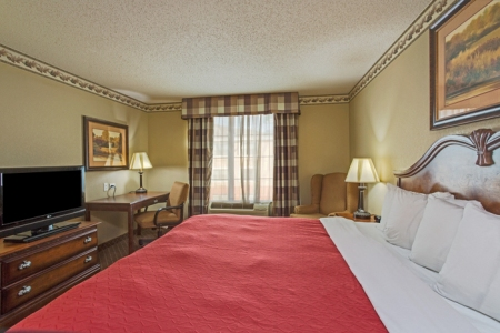 Guest room featuring a king bed with a red comforter and a flat-screen TV