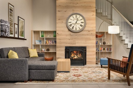 Welcoming hotel lobby with a sectional, an armchair and a clock hung above the fireplace