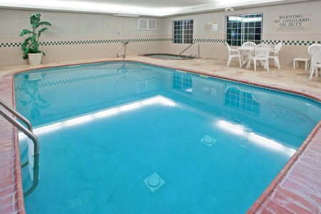 Indoor pool area with white patio furniture
