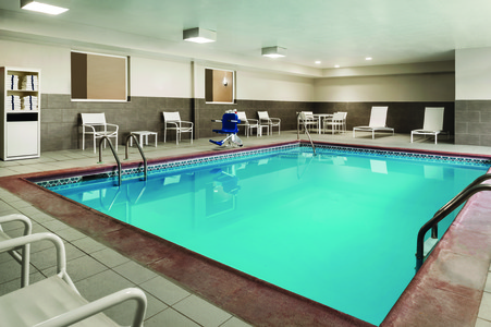 Indoor pool with towels and poolside seating available