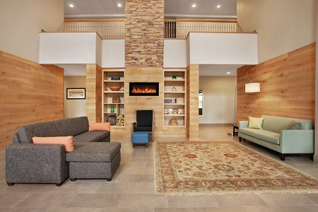 Hotel lobby with a fireplace, a green sofa and a gray sectional