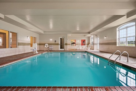 Indoor pool area with fresh towels and a pool chair lift