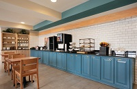 Dining area with juice, pastries, fresh fruit and blue cabinets