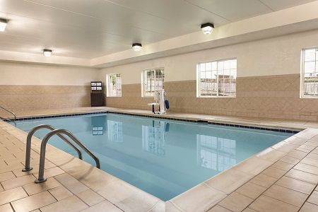 Hotel's indoor pool with a hydraulic chair and towels